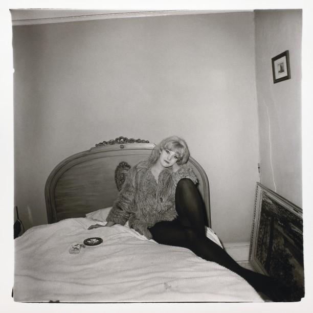Girl in a coat lying on her bed, N.Y.C.