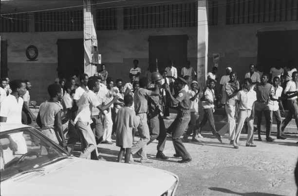 Dawn on February 7th.  As news spreads that Jean-Claude Duvalier is gone, a soldier disarms a Tonton Macoute