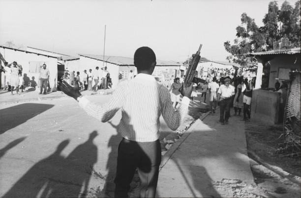An out-of-uniform Tonton Macoute with an Uzi machine gun harasses a crowd